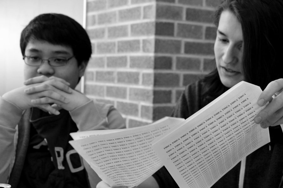 Senior John Horlador and junior Nolan Aguirre read papers covered with coding.