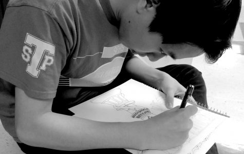"""Junior Matthew Nguyen concentrates on his latest art piece, """"The Queen Bee."""""""