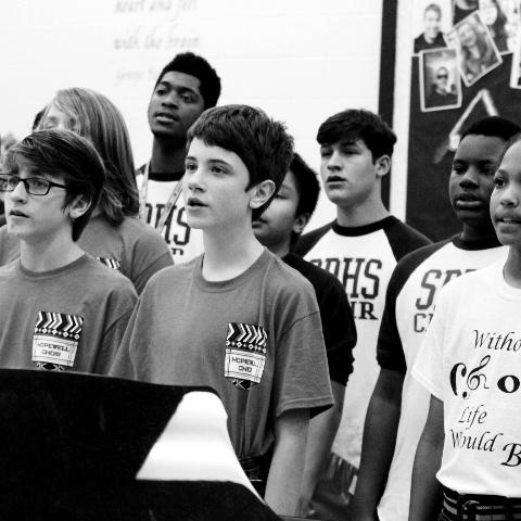 Junior Bryce Mouton (second from right) practices with other choir students before they go on stage at their concert.