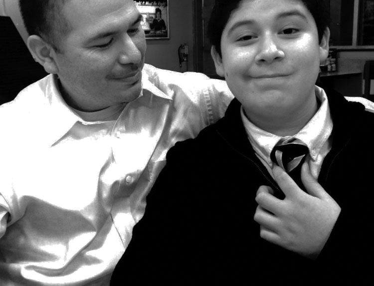 Junior Israel Medina takes a picture with his father during their time together.