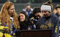Together as a team: Cross country students and coach Allison Coburn cry during their final speech at Kelley's memorial.