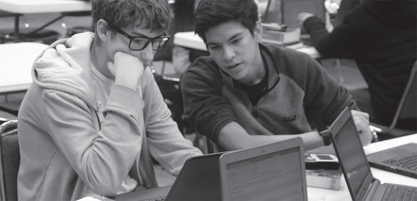 Sharing new findings: Junior Carlos Perez looks over onto junior Caleb Wohn's laptop screen in order to look at recently discovered statistics over spacecraft speeds for their Group 4 project and presentation.